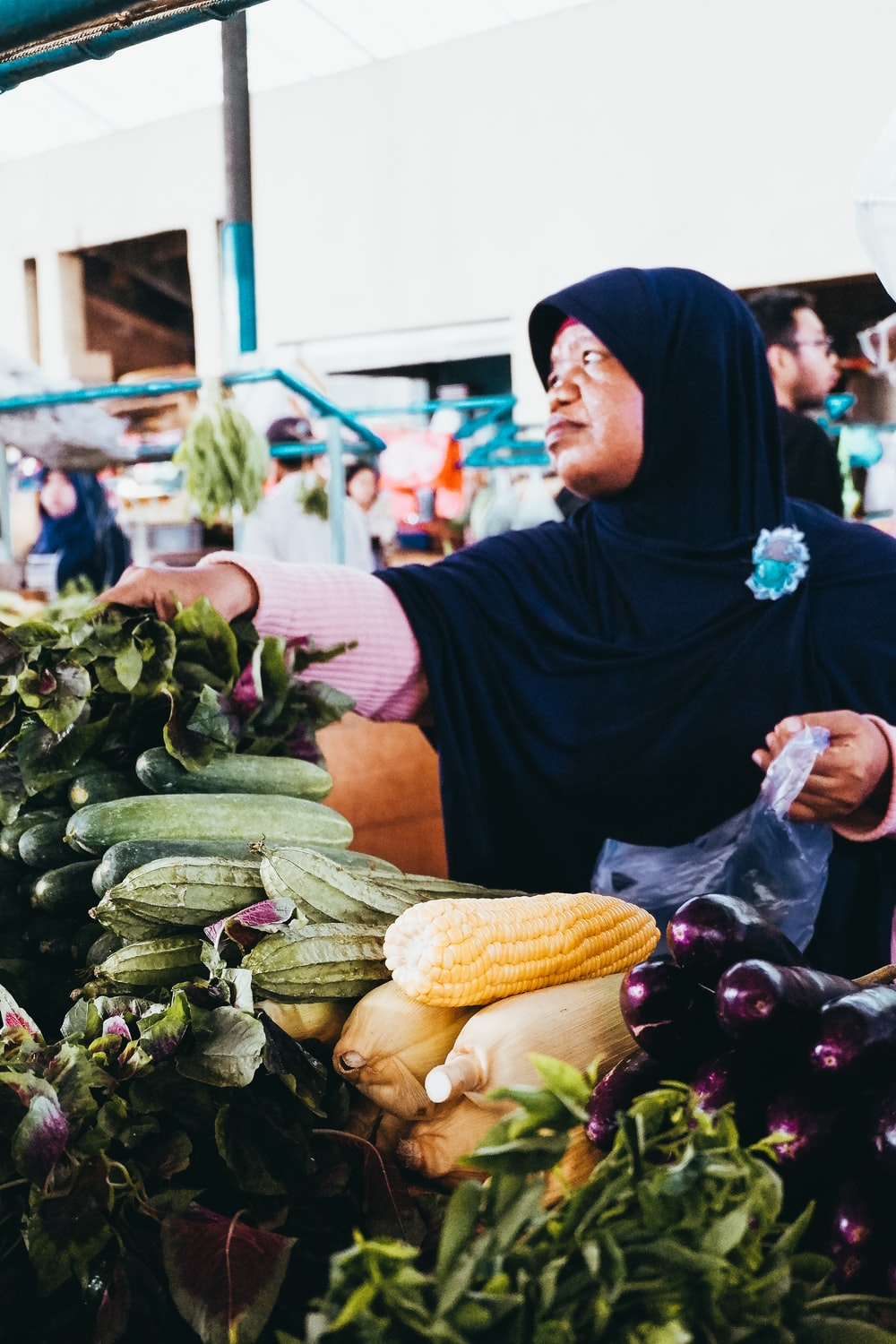 woman in black hijab headscarf selling vegetables