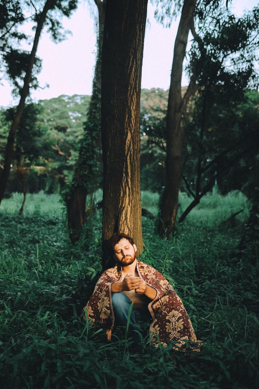 man sitting beside brown tree during daytime