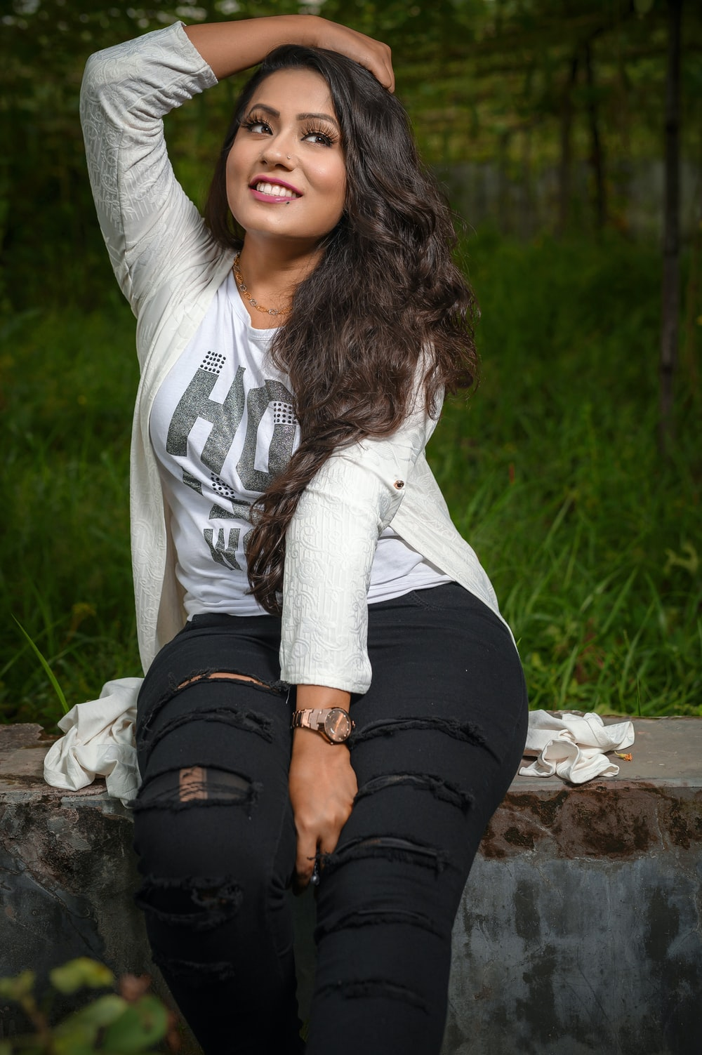 woman wearing white shirt and distressed black jeans