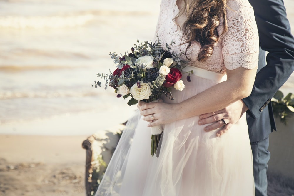 man standing in front of woman holding bouquet of flowers