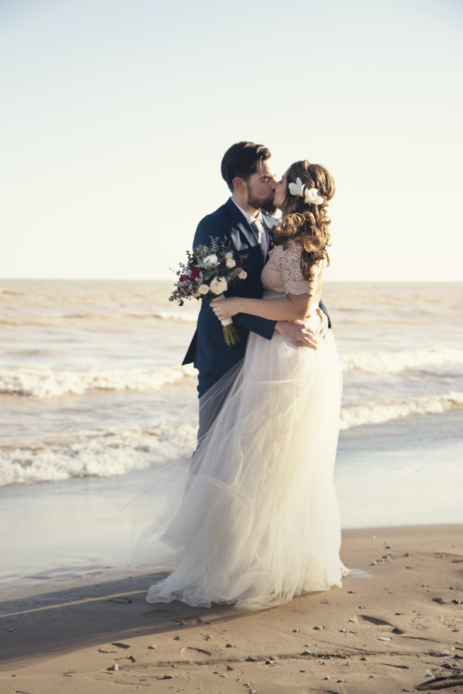 bride and groom standing beside shoreline