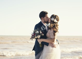 bride and groom standing beside shoreline