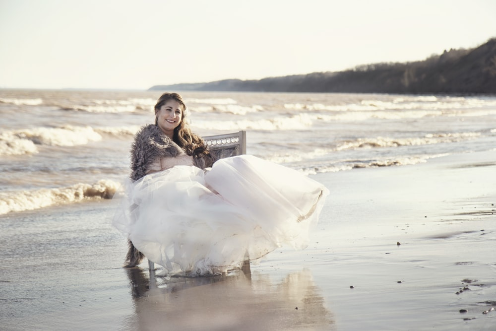 woman sitting on chair on seashore during day