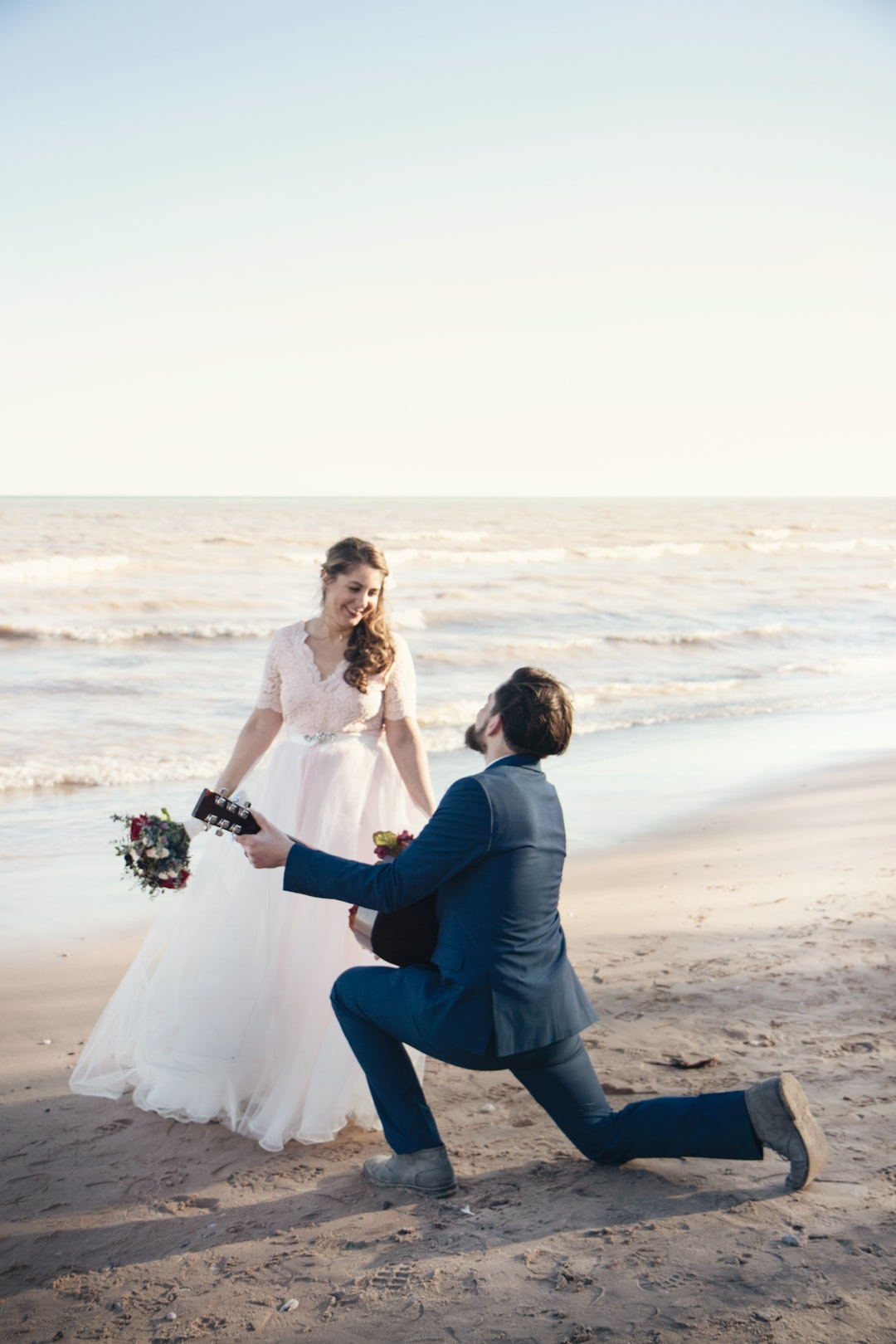 Bride and groom on beach with groom on bended knee with guitar signing a song he wrote for his bride