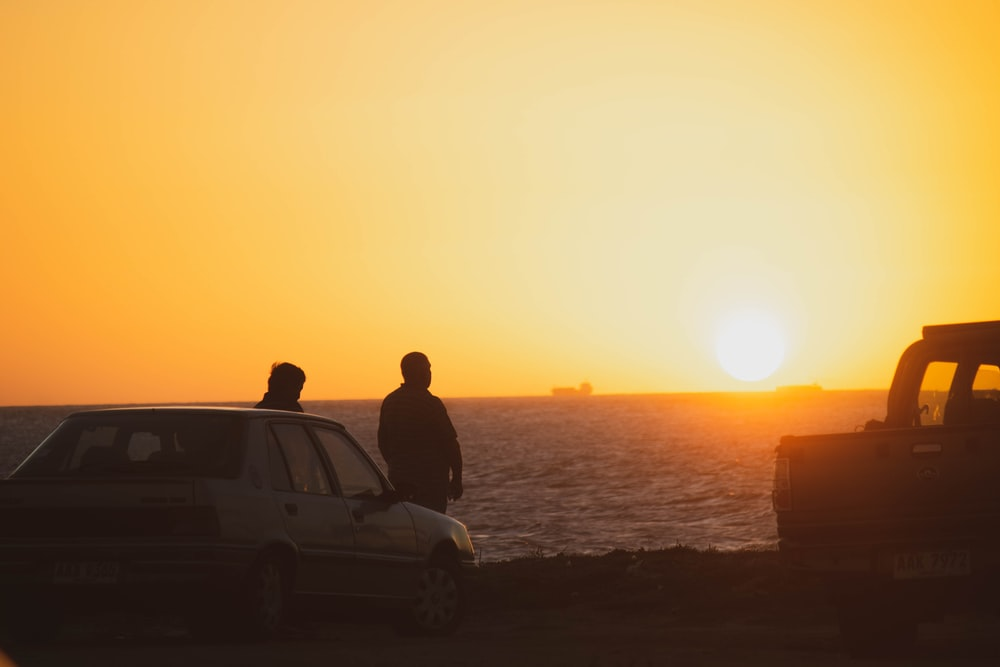 two persons beside car