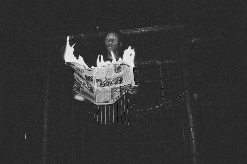 man holding burning newspaper