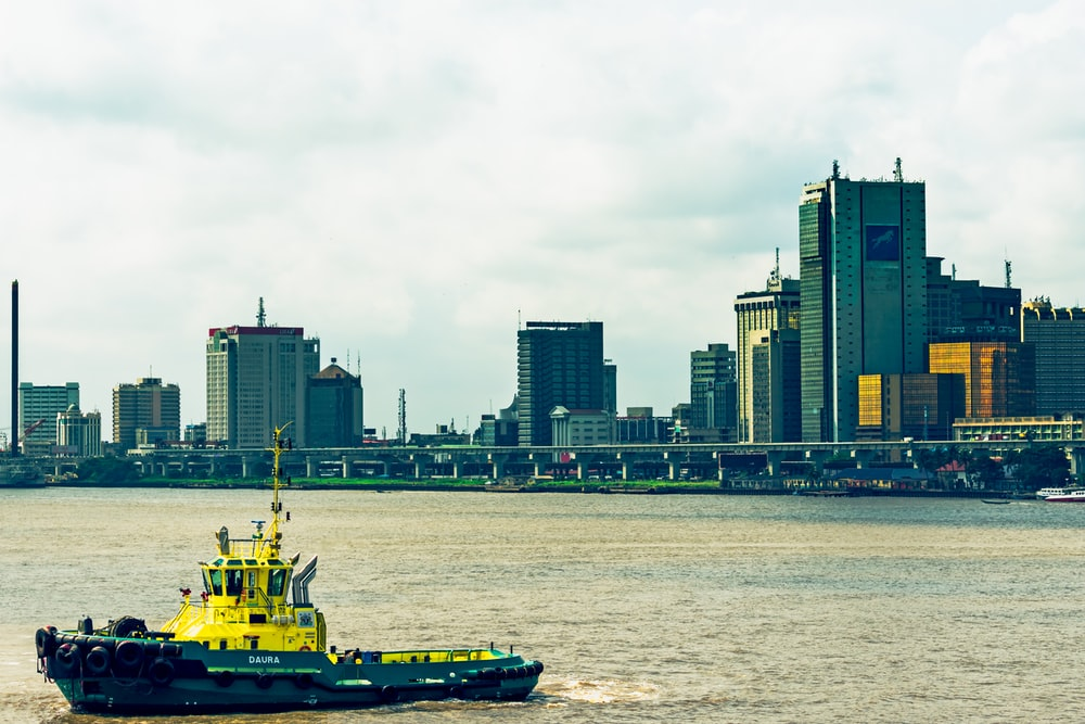 green and yellow boat on sea viewing city with high-rise buildings during daytime