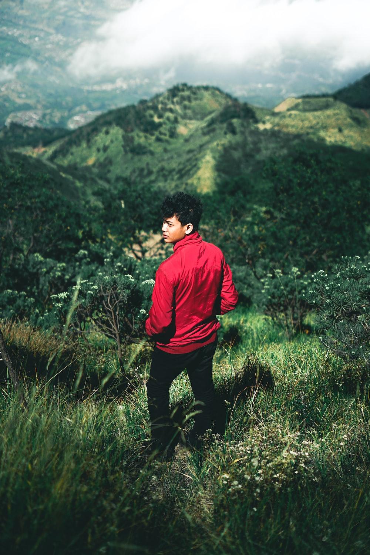 man wearing red jacket standing across green mountain