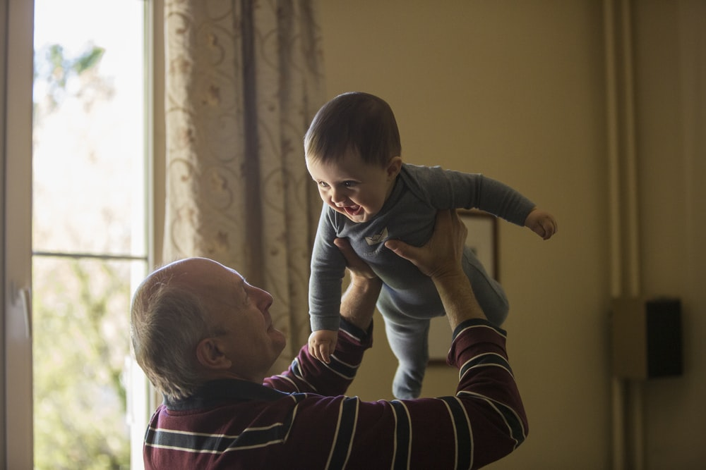 man wearing maroon, white, and blue stripe long-sleeved shirt lifting up baby wearing gray onesie