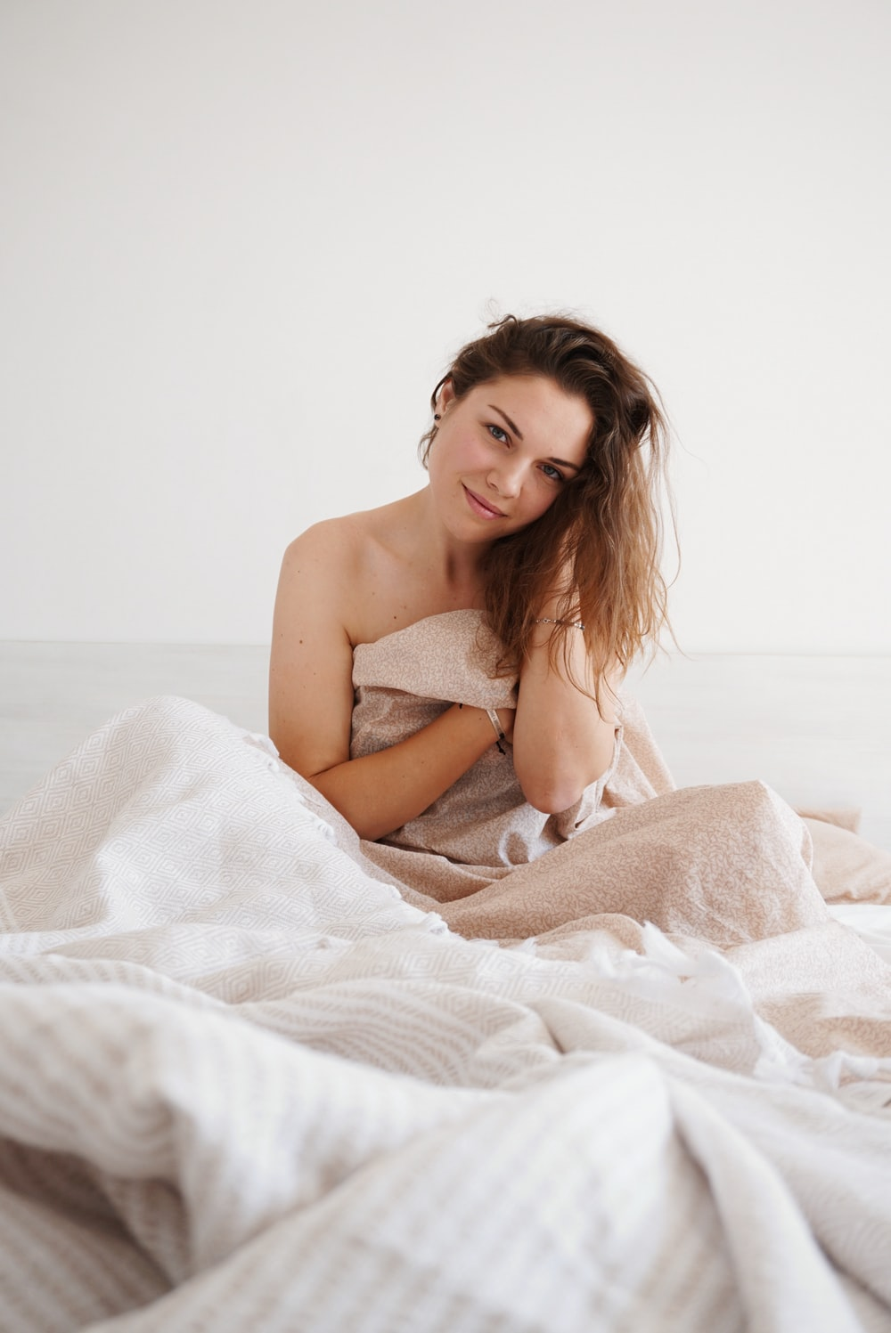 woman sitting in bed under blanket