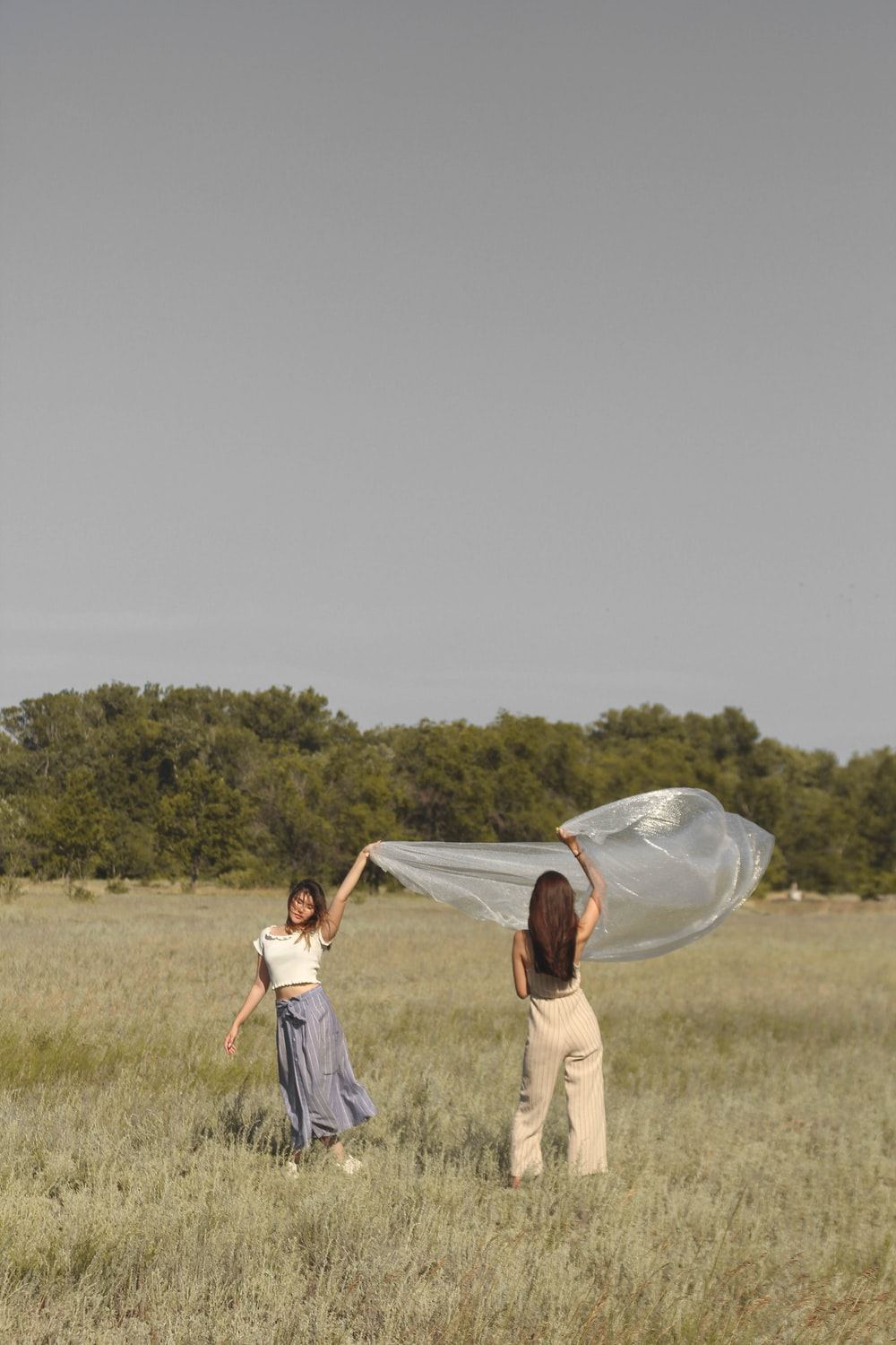 two woman holding blanket