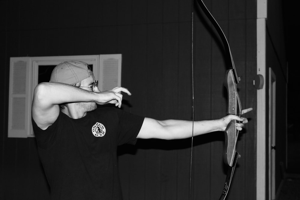 grayscale photo of man holding composite bow
