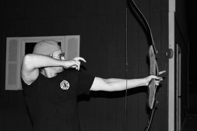 grayscale photo of man holding composite bow archery zoom background