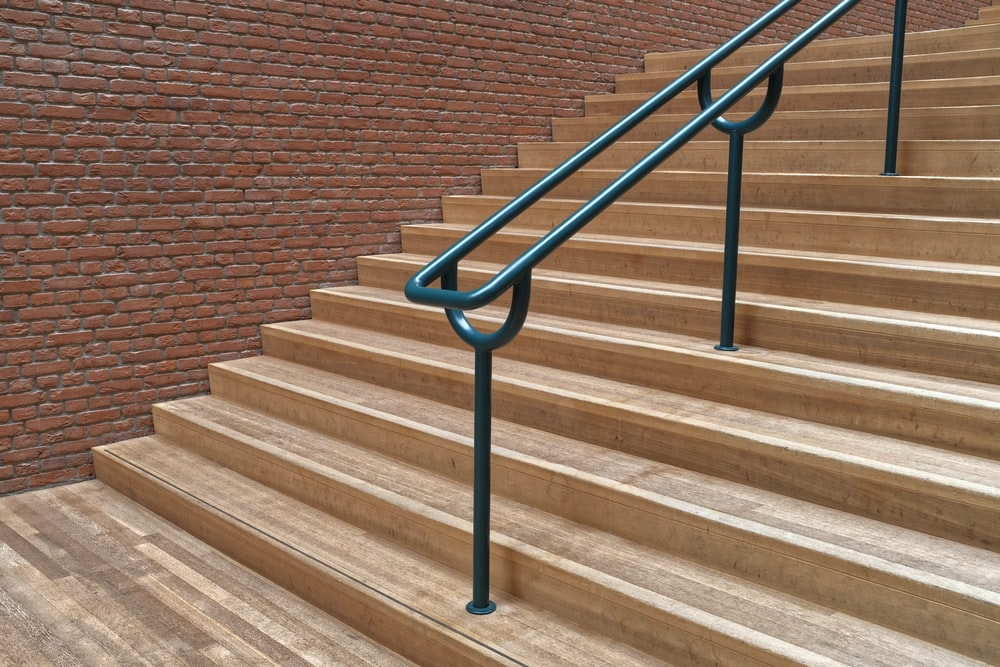 brown concrete staircase with green metal railing