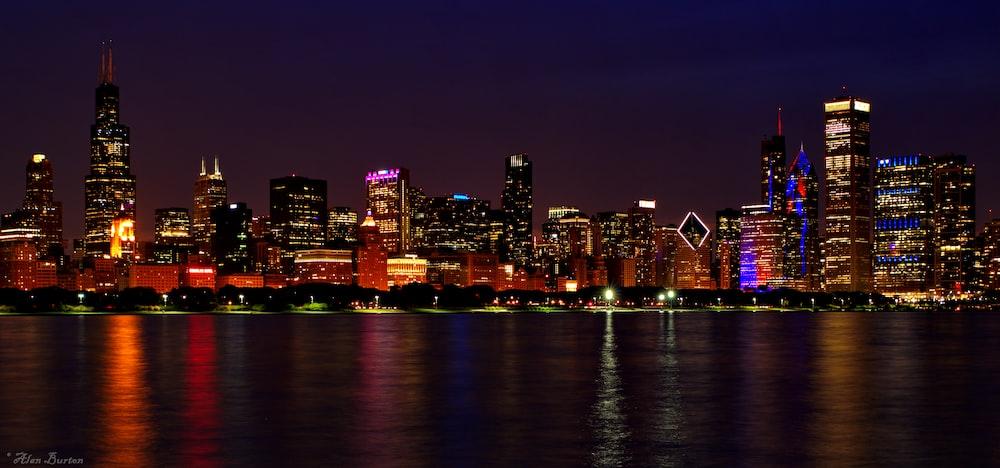 lighted buildings near ocean during nighttime