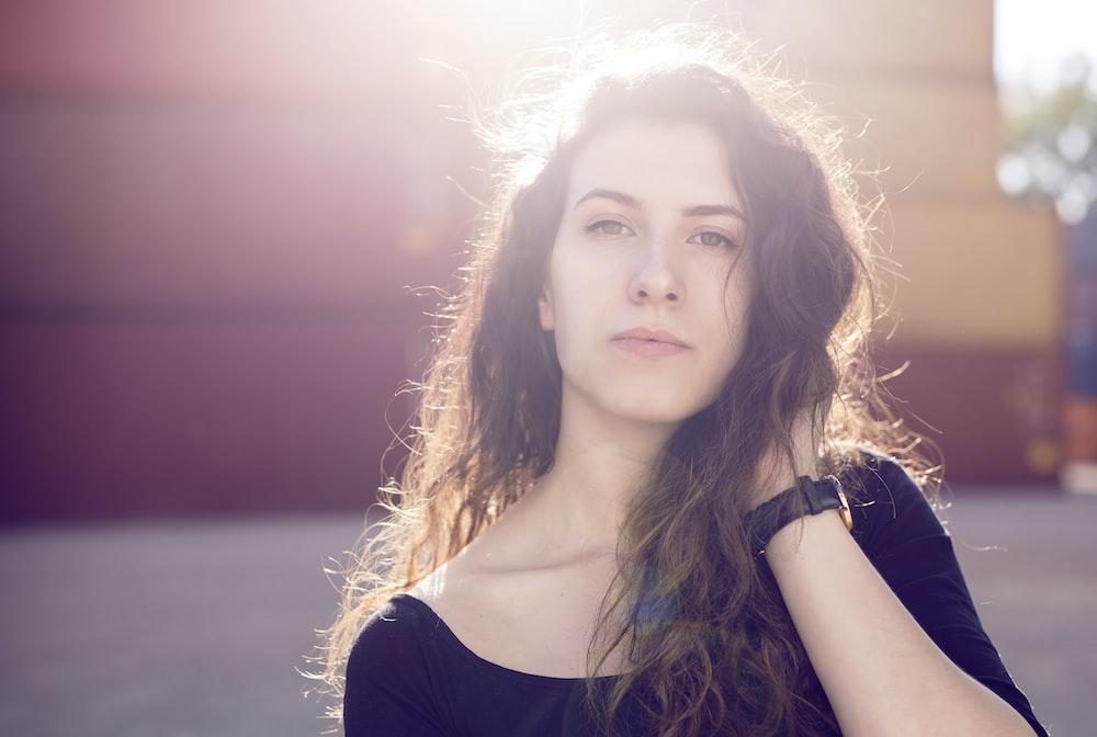 woman wearing black top holding hair