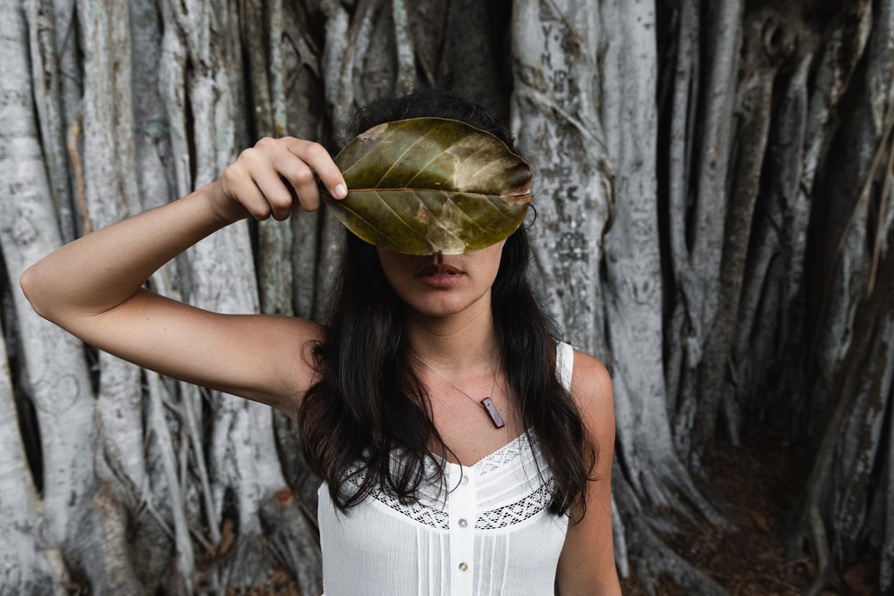 woman covering her face with leaf