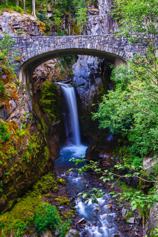 waterfall under stone bridge
