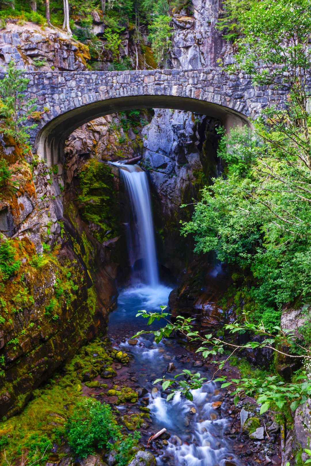 A photo of Christine Falls (in Mt. Rainier). A waterfall under an arch.