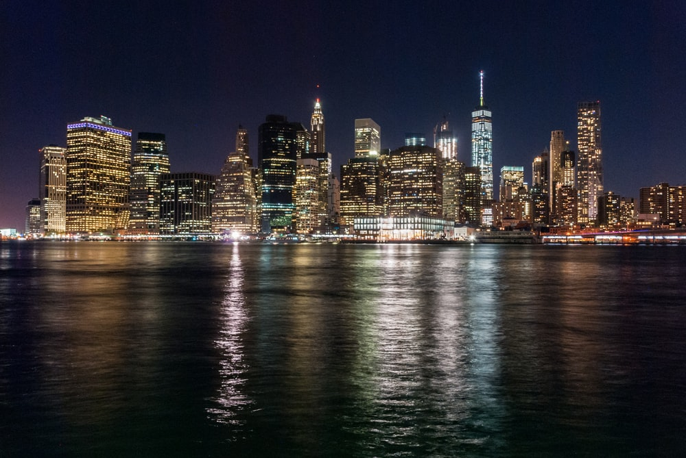 panoramic photo of lighted cityscape at night facing ocean
