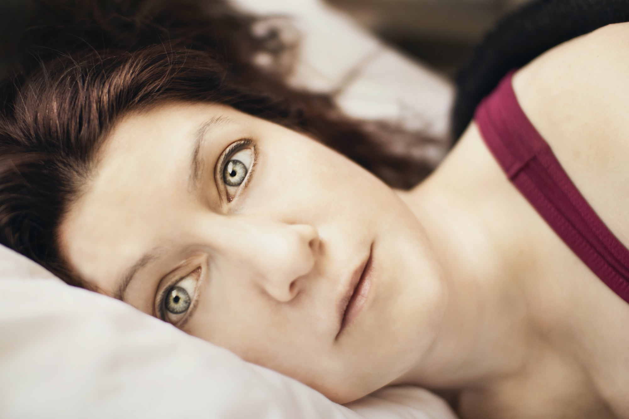 Young woman lies in bed, haunting eyes wide open following a night of insomnia, and ponders what today will bring - more of the same exhaustion, depression and sadness following the separation from her husband?