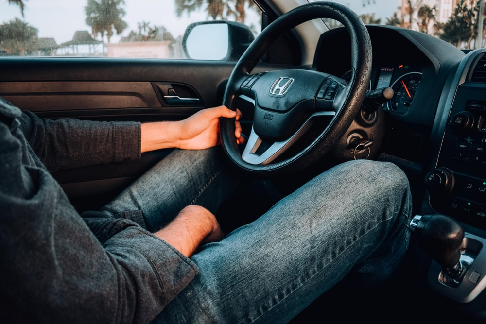 person holding black Honda car steering wheel