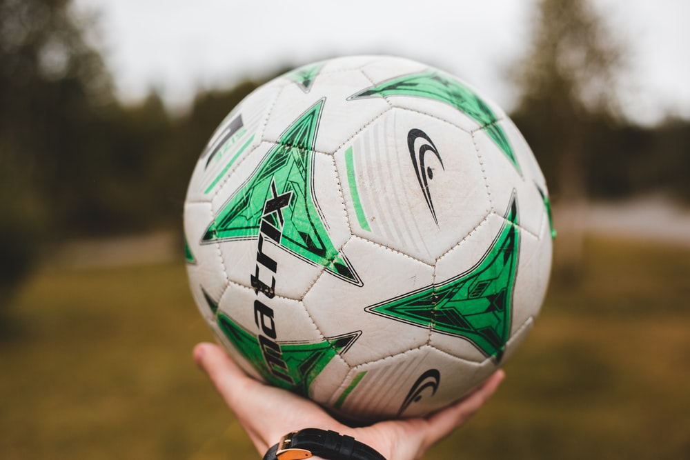 person holding white and multicolored soccer ball