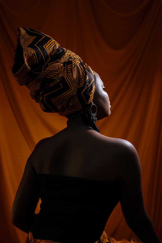 woman facing yellow curtain