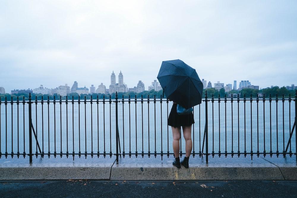 person holding umbrella near sea