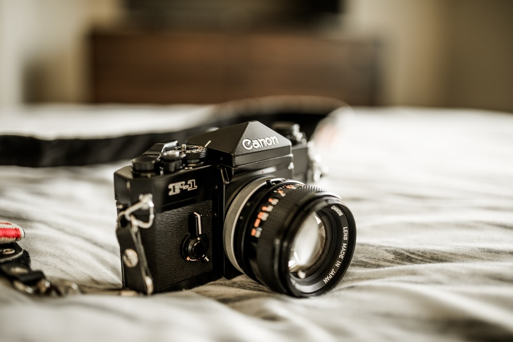 closeup photo of Canon DSLR camera on bed