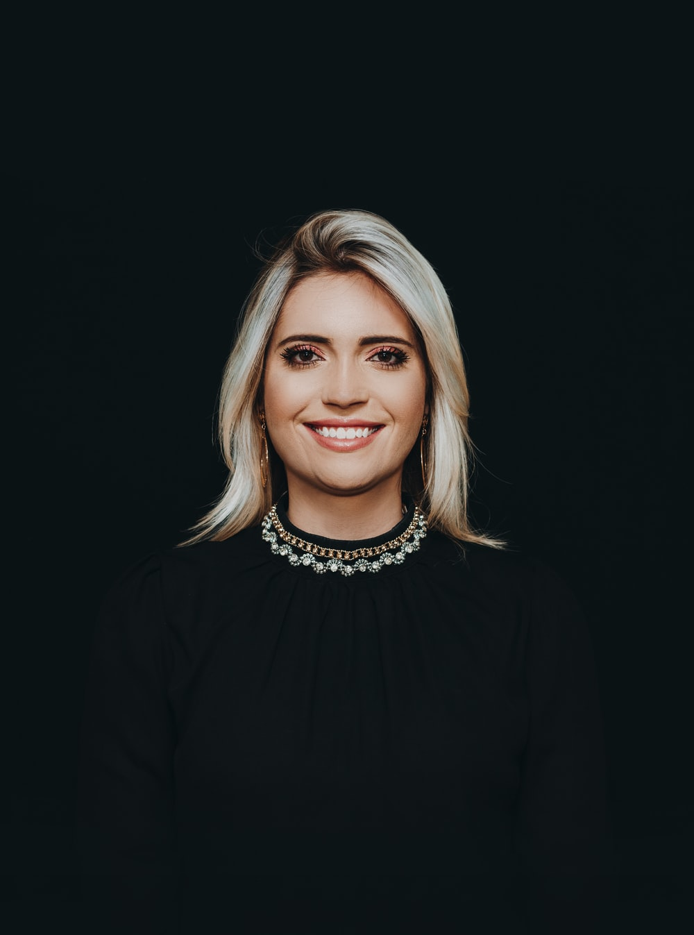 smiling woman wearing black crew-neck top
