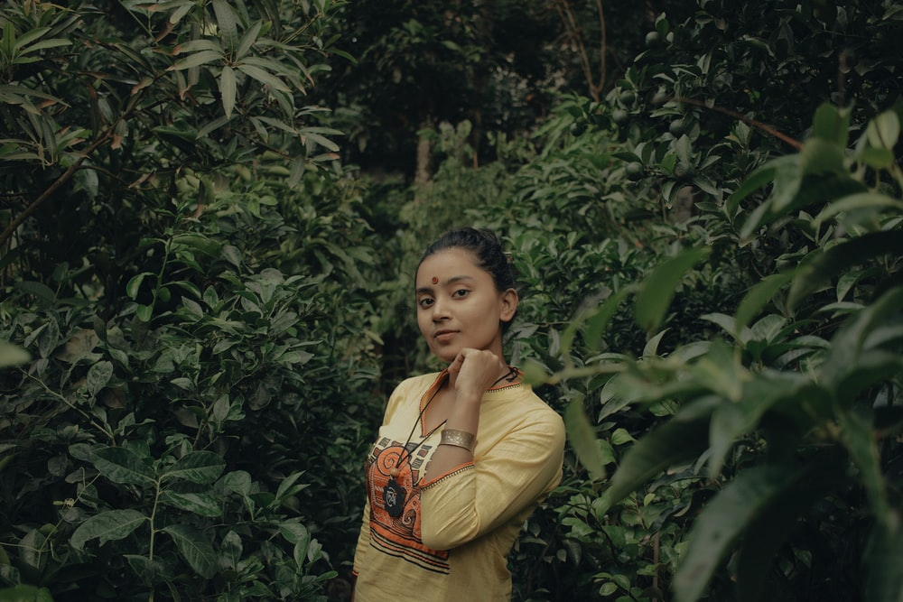woman wearing yellow long-sleeved shirt surrounded by plants