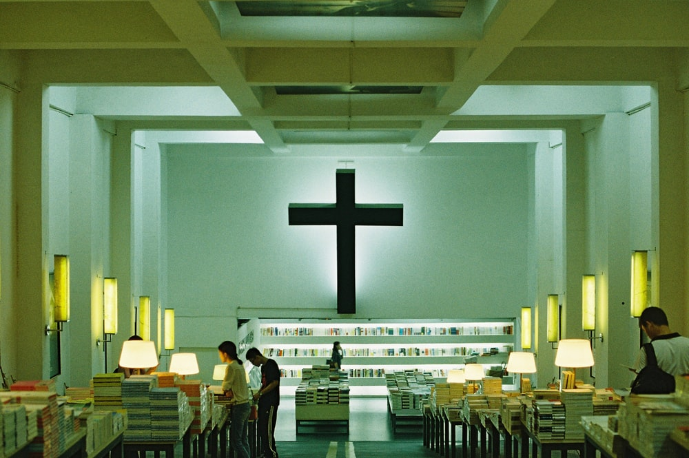 people standing inside building with black cross on wall