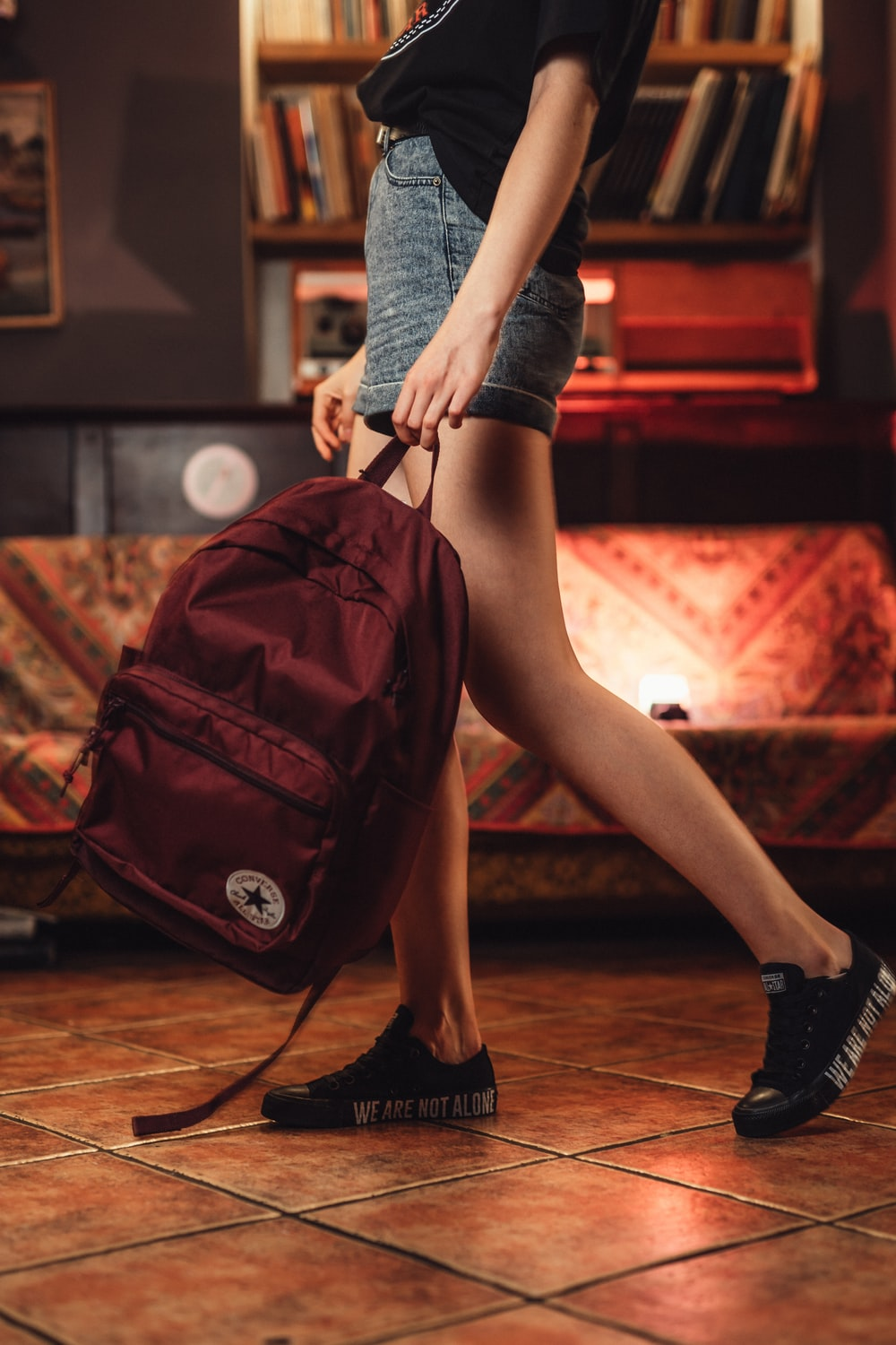 woman carrying maroon backpack