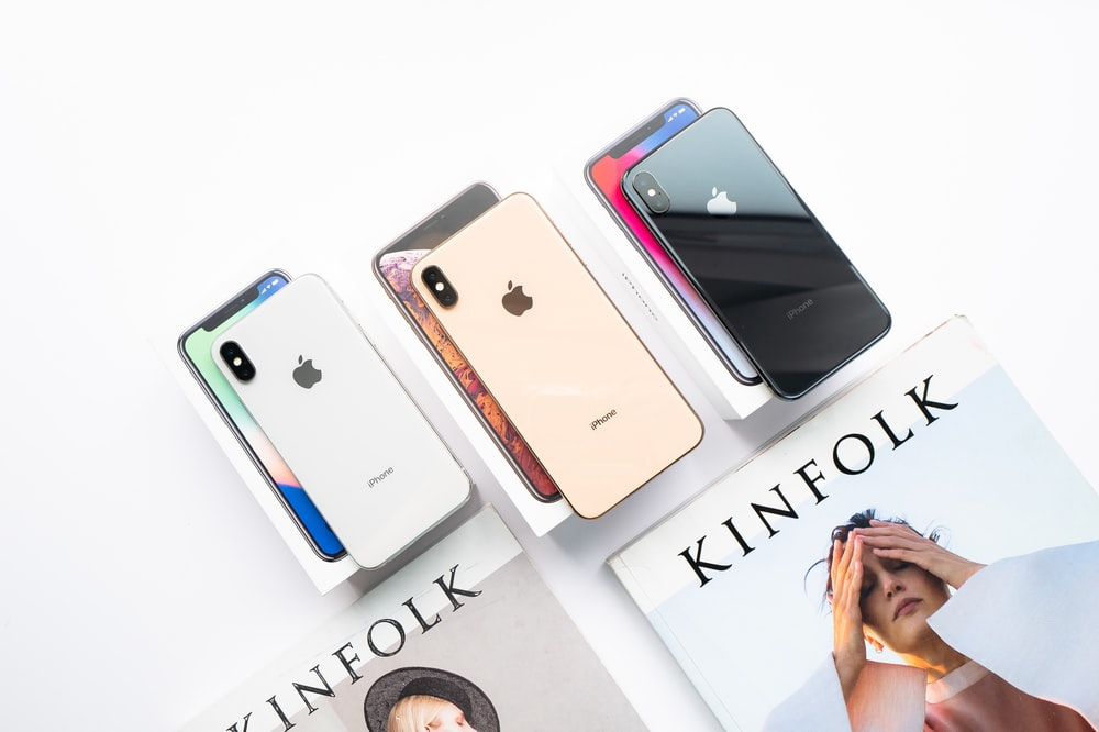 three assorted-color of iPhone Xs on boxes