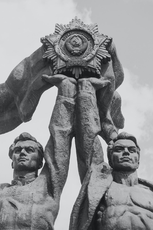 two men raising star statue