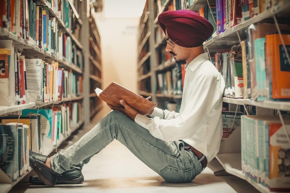 man sitting in front of bookshelf