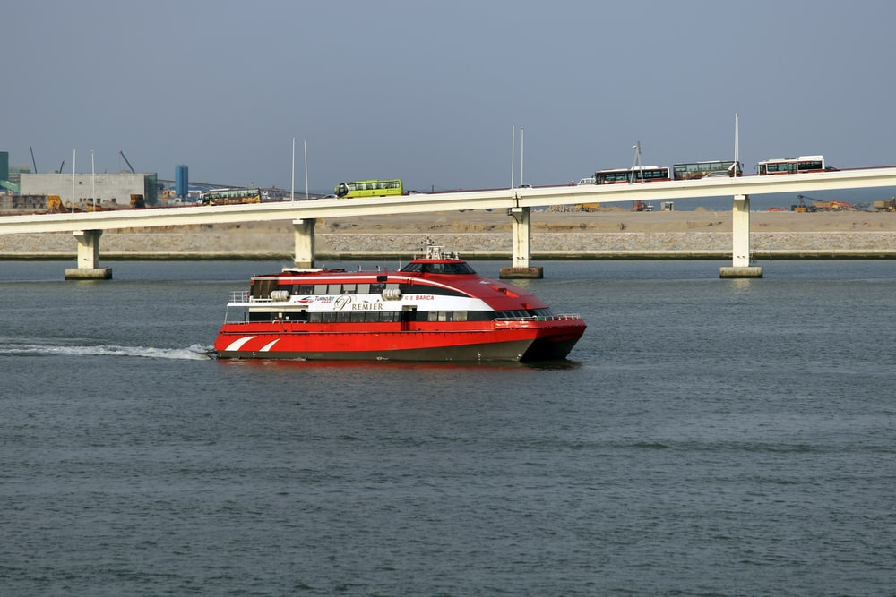 red passenger boat near concrete bridge
