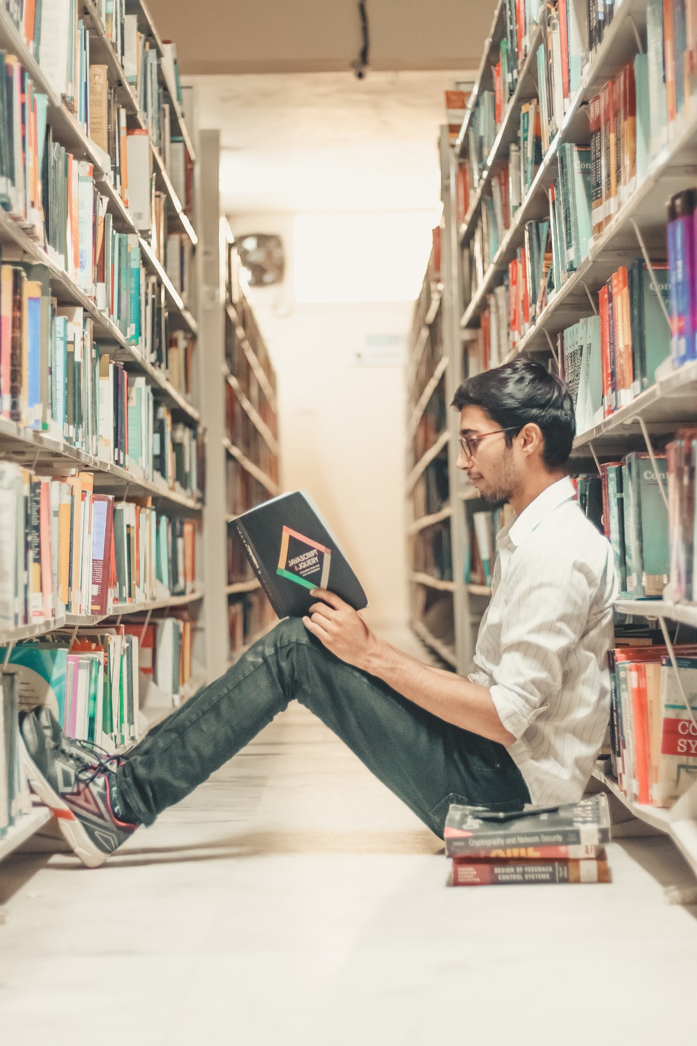 man reading book on the library