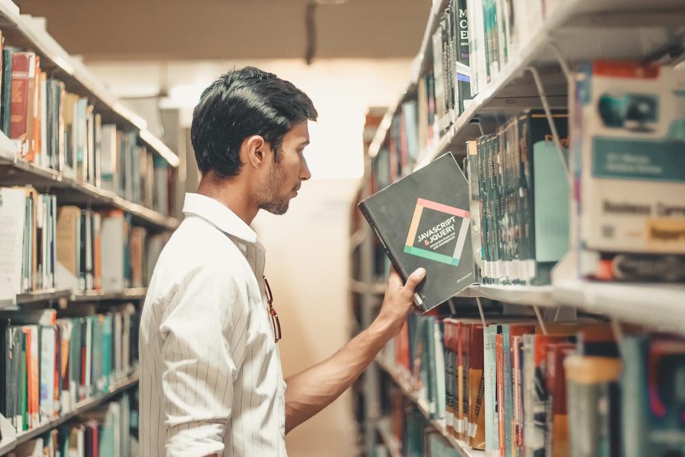 man holding black reading book