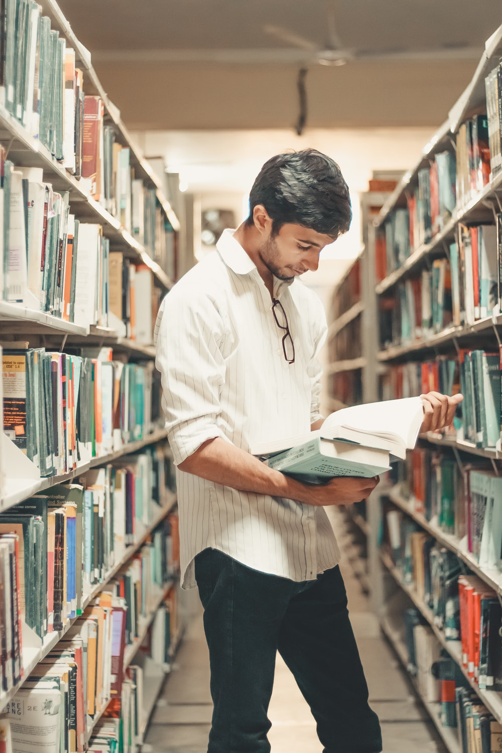 man holding and reading book while standing inside library