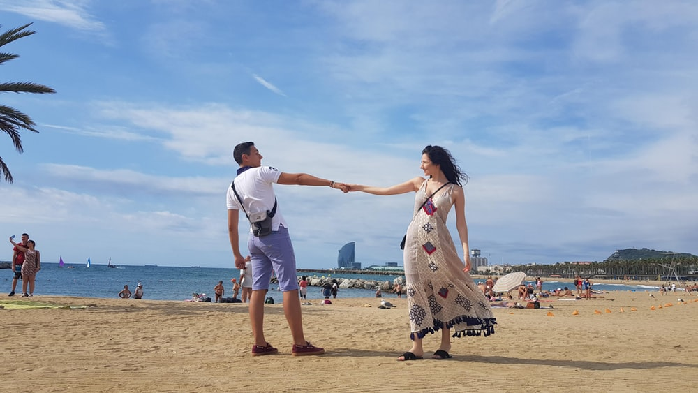 man and woman holding hands on beach