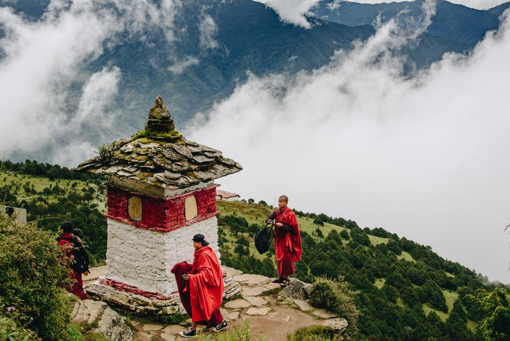 monks on red and white temple