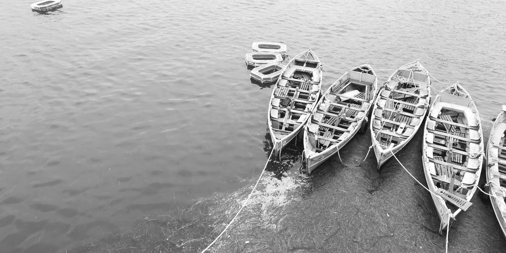 grayscale photography of boats in body of water