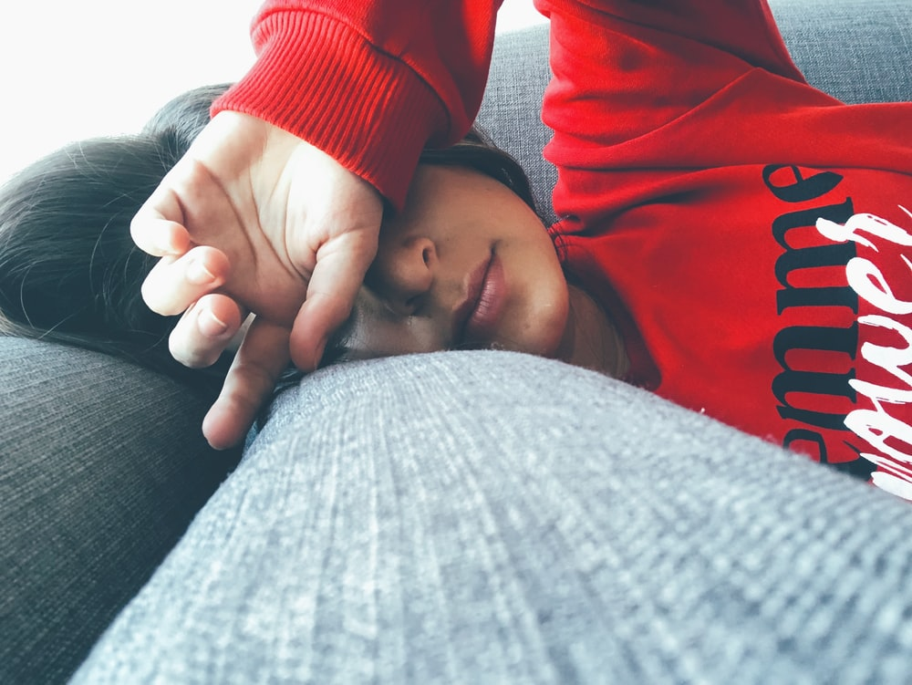 woman wearing red sweater lying on grey suface