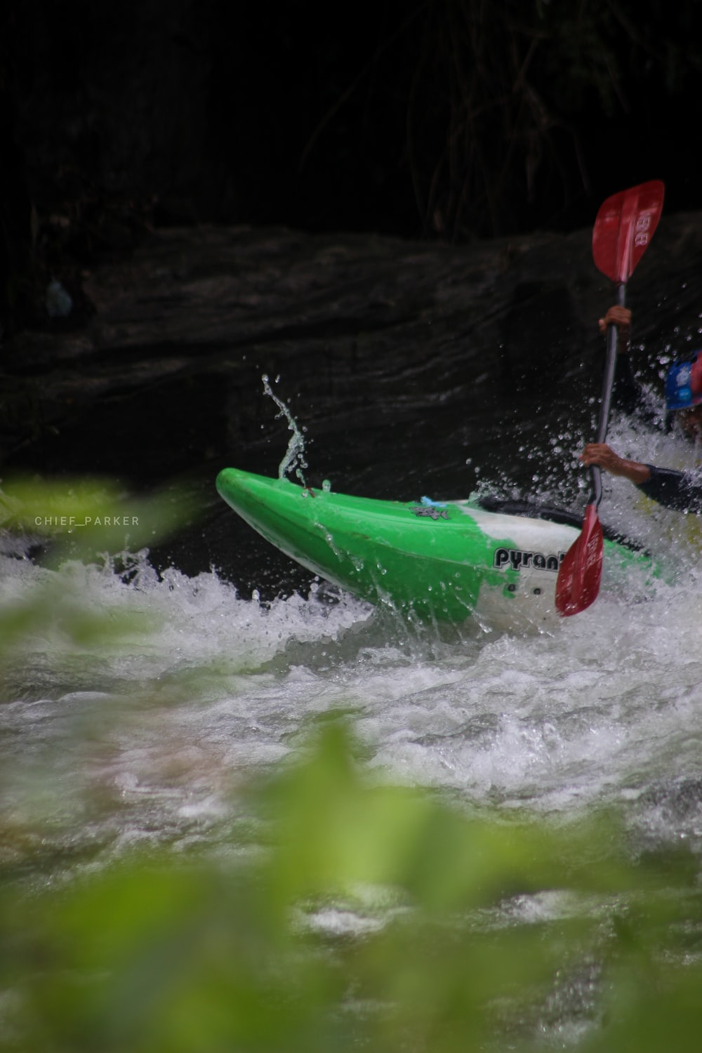 person on green and white kayak