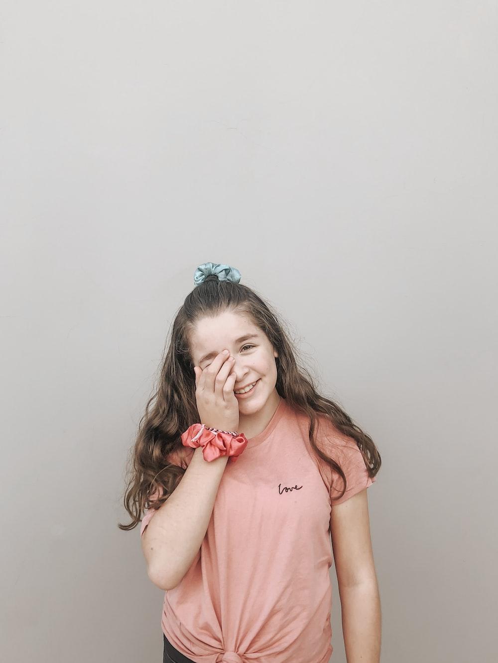 smiling girl wearing pink sleeveless top