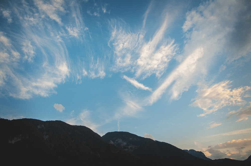 landscape photography of black and gray mountain under white cirrus clouds