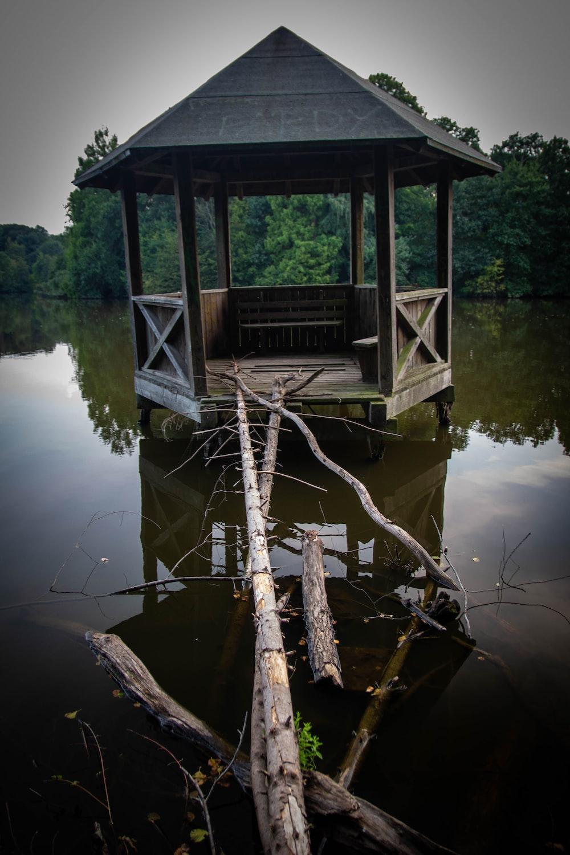 gray wooden gazebu on calm water