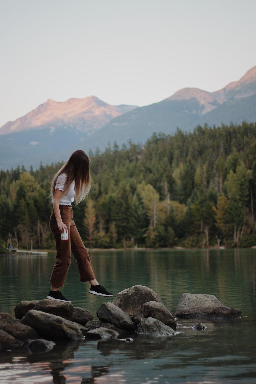 woman stepping on gray rocks near lake viewing mountain during daytime